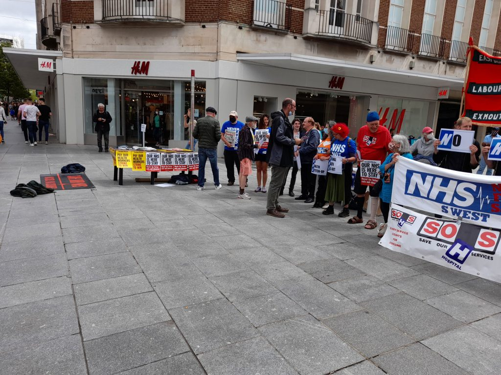 A line of protesters curved around a public square with banners and placards reading Our NHS is Not for Sale